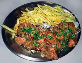 Leckere regionale Spezialität aus Schweinefleisch und Muscheln, mit Piri-Piri